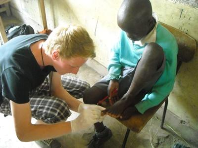 A medical volunteer helps a schoolboy with his injury in Kenya.