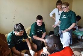 A high school student volunteering in Kenya helps with disinfecting a child's wound at a Medicine community outreach.