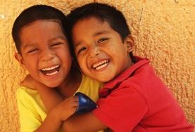 Two children laugh excitedly at a placement in Mexico