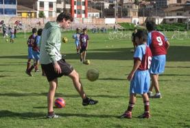 A coaching volunteer plays with children