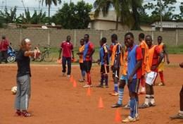 A volunteer works with a local football team in Togo, leading them through a drill to improve their ball skills and technique.
