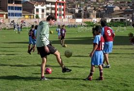 A Sports volunteer teaches school children his technique for kicking a football on our Multi-sports project in Peru.