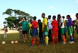 A volunteer coaches students through a football drill during a school sports lesson in Jamaica.
