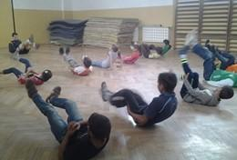 A School Sports volunteer leads a stretching class during a physical education lesson with school children in Romania.