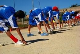 An Athletics volunteer leads a group of young athletes through a stretching exercise before they compete in a track race.