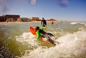 A volunteer works with disadvantaged children, teaching them to surf and promoting exercise.
