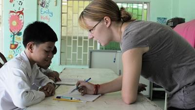 A Teaching volunteer helps a young student with school work in Cambodia