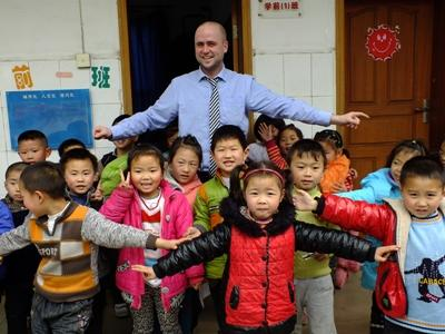 A Teaching volunteer stands with his class in China