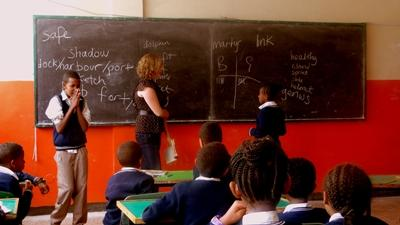 A volunteer teaches a class of enthusiastic children in Ethiopia