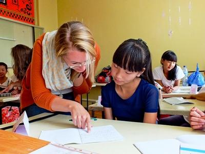 A volunteer helps her student with her school work in a classroom in Mongolia, Asia