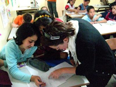 A volunteer helps her students with their homework in Morocco, Africa.