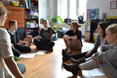 A Projects Abroad volunteer sits with Romanian teenagers in their classrooom