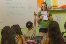 A classroom engages during a lesson with a Teaching volunteer