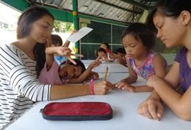 A Teaching volunteer interacts with a student on a placement in the Philippines