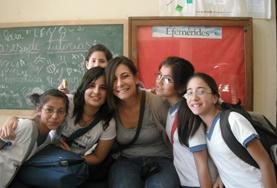 A volunteer poses with students in a classroom on a French Teaching Project in Argentina