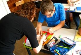 A volunteer French Teacher assists a student on a placement in Romania