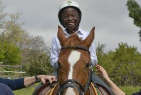 A young boy smiles as he rides his therapy horse during treatment at our volunteer Equine Therapy placement in South Africa.