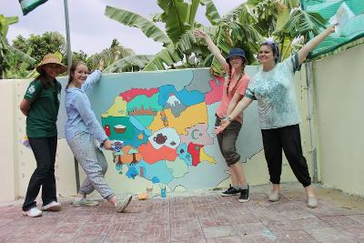 Projects Abroad Care and Community volunteers from Anglia Girl Guides group in the UK paint a mural at a Cambodian school