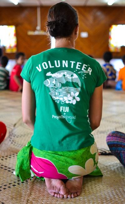 Projects Abroad Care volunteer on a work experience placement kneels among Fijian children during a holiday school graduation ceremony